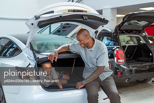 UK, Father and son (8-9) sitting in car trunk in showroom - p924m2300785 by Monty Rakusen