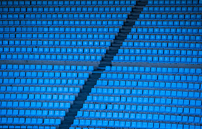 Empty blue seats in row at stadium - p1166m2025136 by Cavan Images