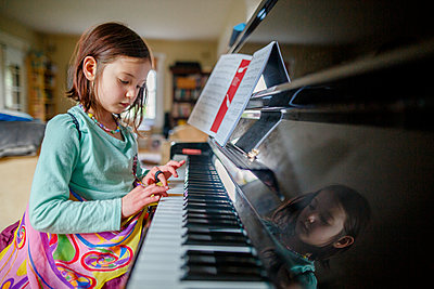 A little girl in butterfly wings sits at piano playing music indoors - p1166m2261266 by Cavan Images