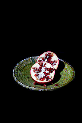 Pomegranate halved on old bowl  - p1248m2209172 by miguel sobreira
