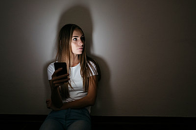Young woman at home sitting on floor using cell phone in the dark - p300m1537407 by Giorgio Fochesato