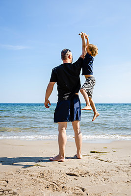 Father and son playing at the beach - p300m2062197 by Julia Otto