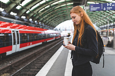 Redheaded young woman with coffee to go waiting at platform using smartphone, Berlin, Germany - p300m2141008 by William Perugini