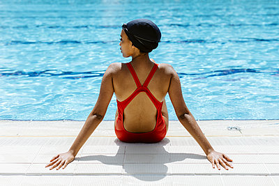 Back view of young woman wearing red swimsuit and swimming cap relaxing at poolside after swimming - p300m2160294 by Sofie Delauw