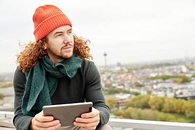 Man looking away while using digital tablet sitting on building terrace against sky - p300m2225530 by Jo Kirchherr