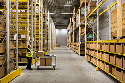 Full length side view of mature female warehouse worker pushing cart on aisle in industrial building - p426m2018854 by Maskot