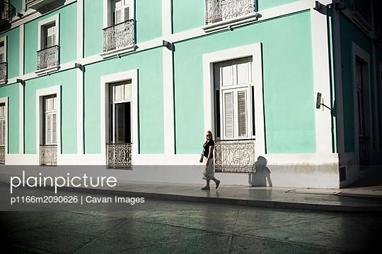 Woman walking in front of turquoise building in Santa Clara, Cuba. - p1166m2090626 by Cavan Images