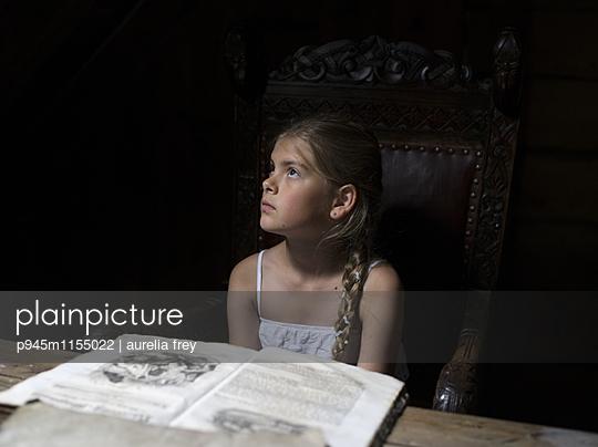 Mädchen mit Märchenbuch beim Tagträumen - p945m1155022 von aurelia frey