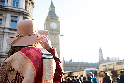 UK, London, rear view of woman wearing a floppy hat looking at Big Ben - p300m2103817 von Ivan Gener