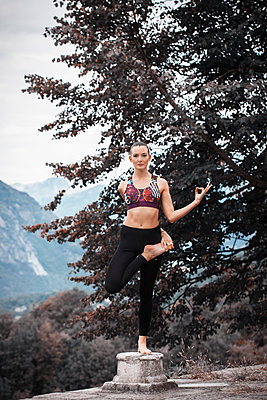 Woman practicing yoga, balancing on one leg on top of plinth, mountain landscape, Domodossola, Piemonte, Italy - p429m2069171 by Guido Cavallini