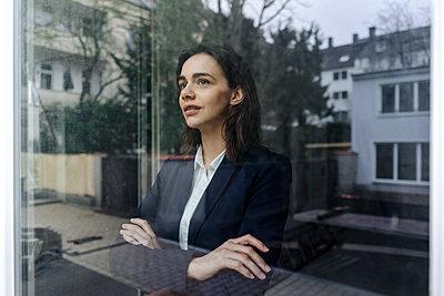 Frau blickt aus dem Fenster - p586m1492132 von Kniel Synnatzschke