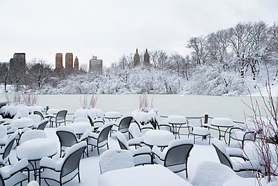 Tables and chairs in snowy urban park - p924m807169f by Ditto