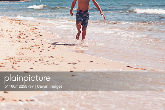 Lower body - boy running on the beach. - p1166m2255797 by Cavan Images