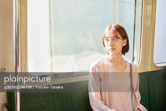 Young Japanese woman on a train - p307m2296758 by Yosuke Tanaka