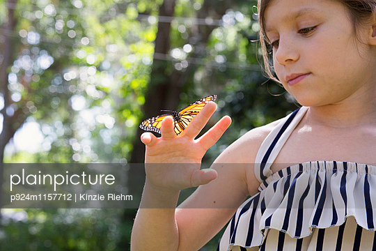 Girl holding monarch butterfly on finger - p924m1157712 by Kinzie Riehm