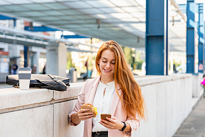 Close up of young professional woman with red hair eating a wholegrain sandwich on the go in the city; Florence, Italy - p300m2290499 von Emma Innocenti