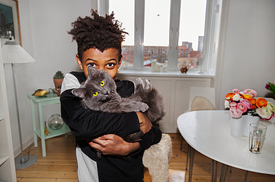 Boy holding cat - p312m2139237 by Pernille Tofte