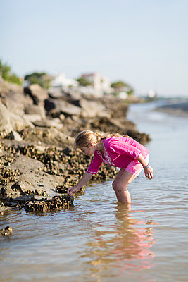 Caucasian girl exploring on rocky beach - p555m1415322 by Marc Romanelli