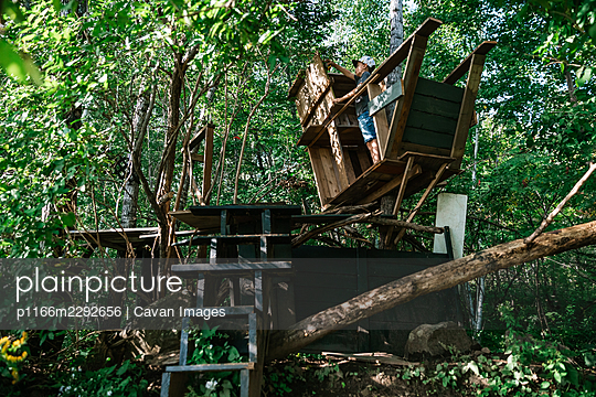 8 years old boy building a treehouse in the forest during summer - p1166m2292656 by Cavan Images