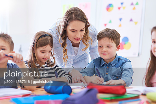 plainpicture - plainpicture p300m1587318 - Teacher helping pupils with... - plainpicture/Westend61/gpointstudio