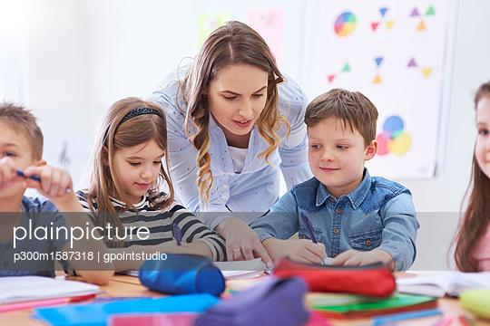 Teacher helping pupils with their tasks in class - p300m1587318 von gpointstudio