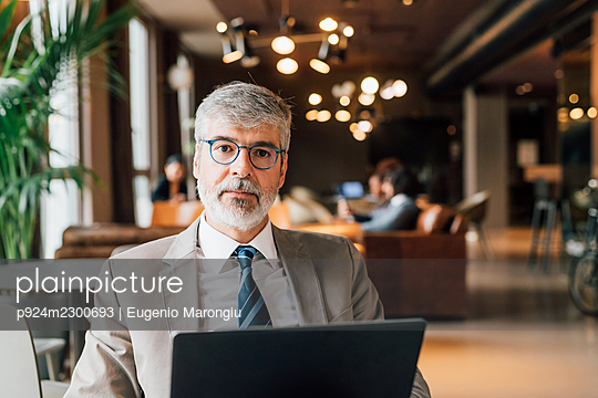 Italy, Portrait of businessman with laptop in creative studio - p924m2300693 by Eugenio Marongiu
