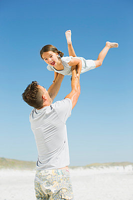 Father lifting daughter overhead on beach - p1023m837192f by Dan Dalton
