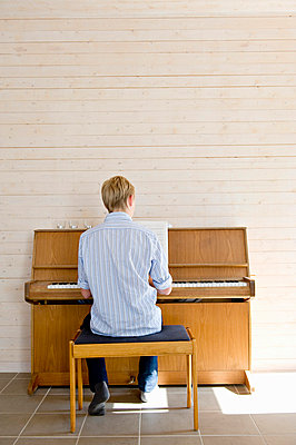 Rear view of a teenage boy playing the piano - p1025m780261f by Björn Andrén
