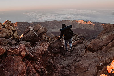 A male hiker walks on trail over the clouds at sunrise,El Teide - p1166m2124326 by Cavan Images