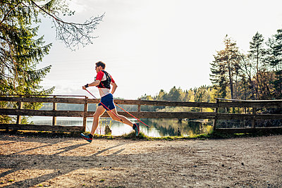 Man running at the lakeside, Forstsee, Carinthia, Austria - p300m2159932 by Daniel Waschnig Photography