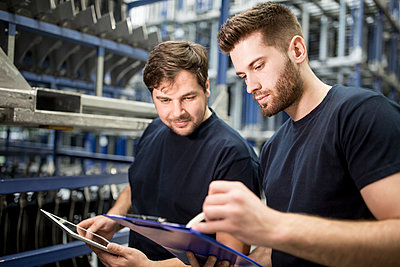 Two workers with clipboard and tablet in factory warehouse - p300m2246000 by Westend61