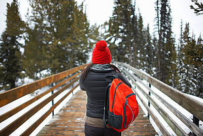 Rear view of hiker on bridge, Banff, Canada - p429m1417890 by Peter Muller