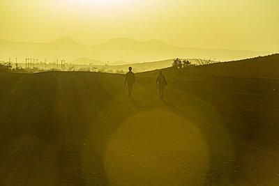 Men walking at sunset, Damaraland; Kunene Region, Namibia - p442m2177309 by Dosfotos