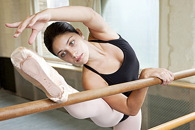 Ballerina stretching at barre - p9245493f by Image Source