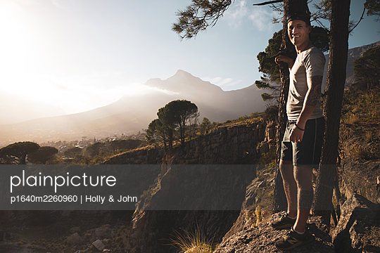 Sporty man in mountain landscape in the sunshine - p1640m2260960 by Holly & John