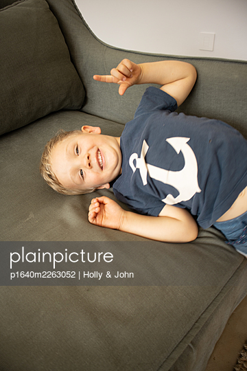 Blond boy fooling around on the sofa - p1640m2263052 by Holly & John