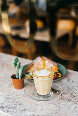 Close-up of fresh breakfast served by potted plant on table at cafe - p1166m2025187 by Cavan Images