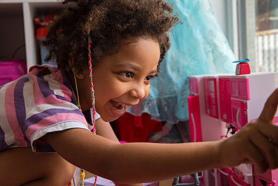Mixed race little girl smiling in a colourful playroom, curly hair - p1166m2261921 by Cavan Images