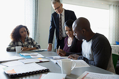 Financial advisor with paperwork meeting with family at dining room table - p1192m1201898 by Hero Images