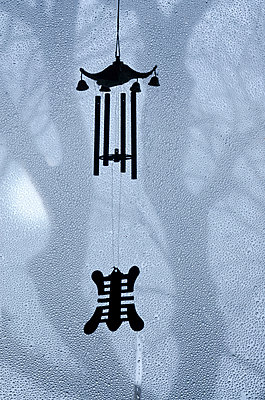 Silhouetted Wind Chimes in Rainy Window onto Trees - p1562m2254549 by chinch gryniewicz