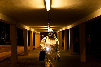 Senior woman wearing protective suit and mask in the city at night - p300m2170120 by Eloisa Ramos