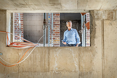 Thoughtful architect with digital tablet while standing at construction site - p300m2256448 by Peter Scholl