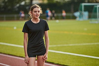 Portrait of teenage girl standing on running track - p312m1442846 by Johan Alp