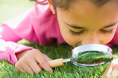 Mixed race girl looking at grass with magnifying glass - p555m1479091 by JGI/Jamie Grill