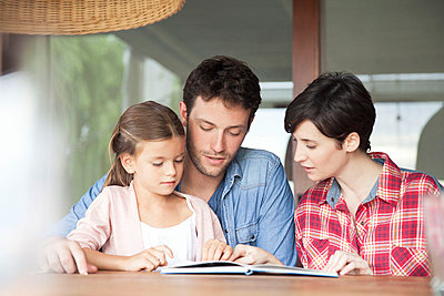 Little girl reading with her parents - p623m1022400f by Sigrid Olsson