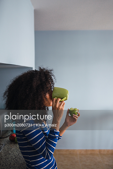 Young woman drinking coffee and eating an apple in her kitchen - p300m2080731 by Kike Arnaiz