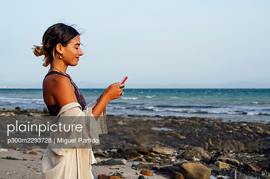 Smiling woman using mobile phone at beach - p300m2293728 by Miguel Partido