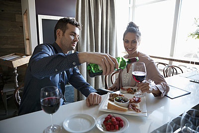Young couple on date pouring red wine at bar - p1192m1567186 by Hero Images