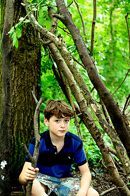 Boy in forest holding branch - p1212m1152951 by harry + lidy