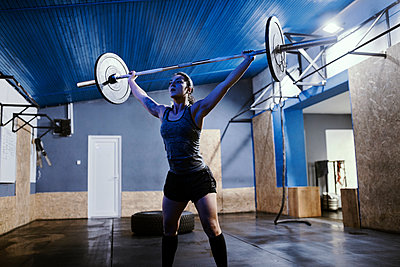 Woman lifting barbell in gym - p300m1581598 by Zeljko Dangubic